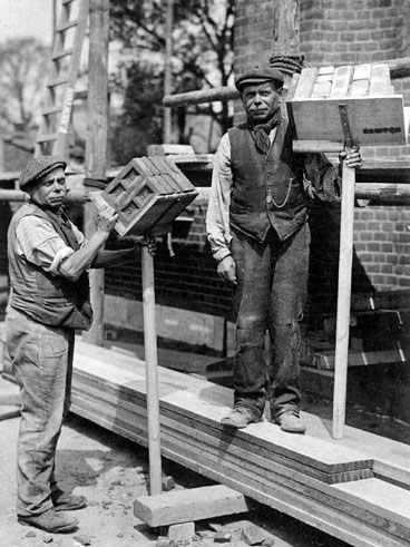 black and white photo of two men carrying bricks